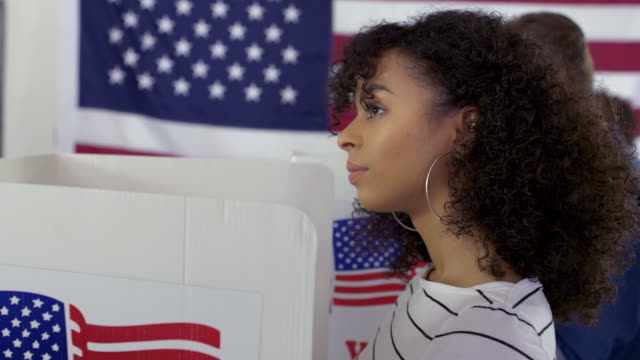 CU Young Latina woman casting vote in booth at polling station video