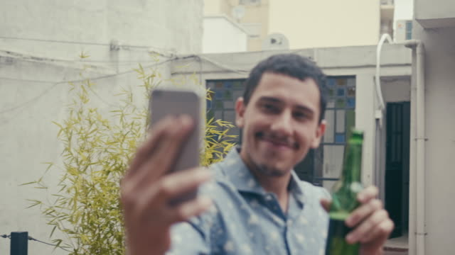 young latin-american male making a selfie with a beer (slow motion) - terrazza video stock e b–roll