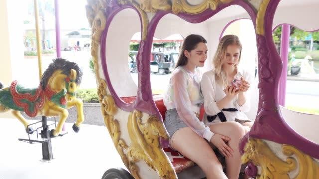 Young lesbian couple at amusement park using smartphone