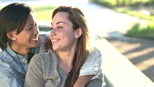 young lesbian couple embracing, talking, smiling - same sex couples stock videos and b-roll footage