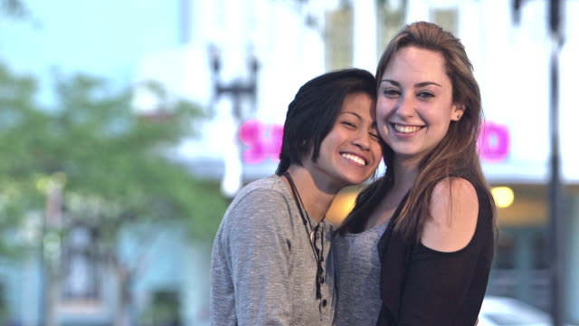 Young lesbian couple walk toward camera holding hands A young, multi-ethnic lesbian couple walking toward the camera along a city street, holding hands, talking and smiling. lgbtqi rights stock videos & royalty-free footage