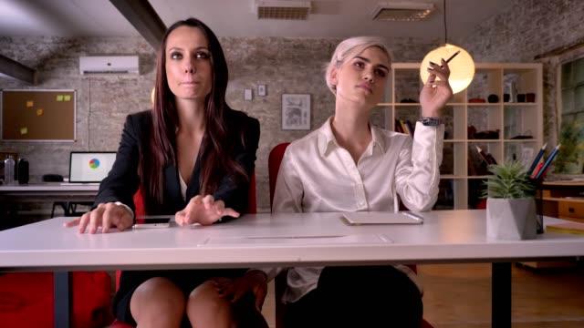 stockvideo's en b-roll-footage met jonge lesbische vrouw knie van de andere vrouw onder bureau in moderne kantoor, lesbische concept, raken geïrriteerd vrouw - verleiding