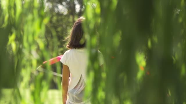 Jovem menina no campo de férias brincando com fita rosa banda a fazer ginástica em grama verde campo slow motion - vídeo