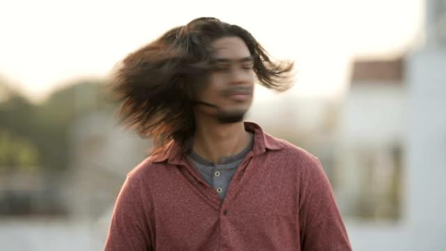 giovane uomo dai capelli lunghi che scuote la testa. - spettinato video stock e b–roll