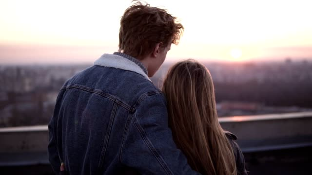 Young long haired woman and red headed man came on the high roof for watching on the city at sunset. Watching the sunset embracing, romantic moment. Backside view Young long haired woman and red headed man came on the high roof for watching on the city at sunset. Watching the sunset embracing, romantic moment. Backside view. young couple stock videos & royalty-free footage