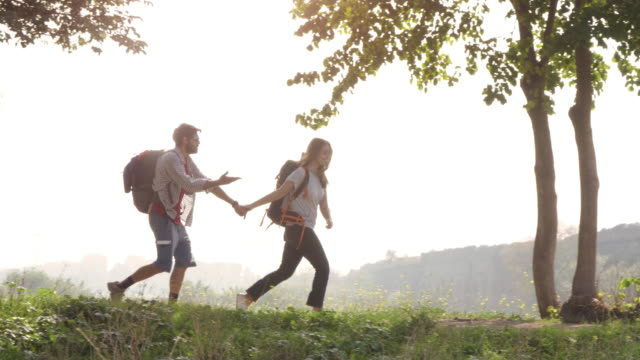 young lovely couple backpackers tourists walking holding hands arrive on hill in front of roman aqueduct arches in parco degli acquedotti park ruins in rome on romantic misty sunrise with guitar and sleeping bag slow motion - турист с рюкзаком стоковые видео и кадры b-roll