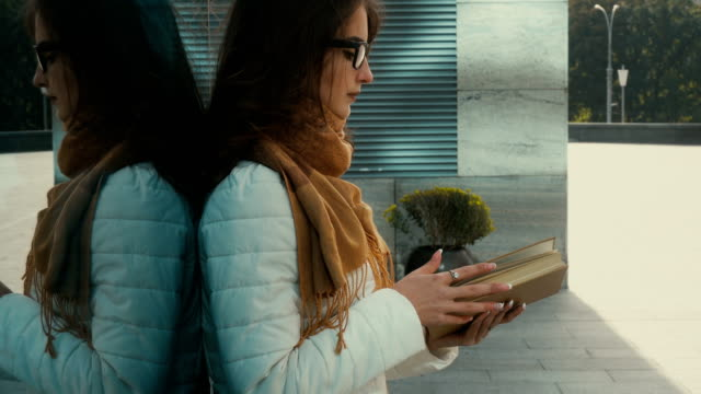 young lovely student girl in glasses reading a book video