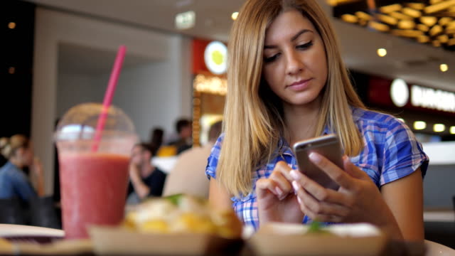 Young Lovely Woman In Blue Checkered Shirt Sits In Cafe Uses Smartphone video