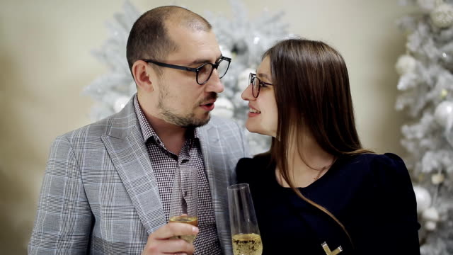 Young loving couple drinking champagne on the Christmas decorations and kissing in Christmas eve.