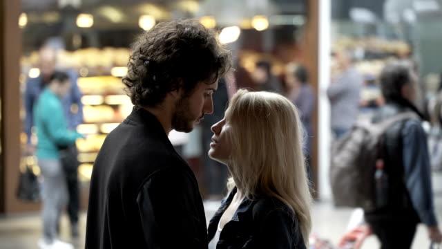 genç seven çift öpüşme ve toplum içinde bir sokakta arka planda insanlarla konuşurken - i̇stasyon stok videoları ve detay görüntü çekimi