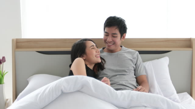 Young loving couple in the bed and Romantic couple in love on bedtime and happiness concept video