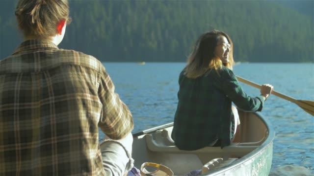 junge liebende paar entfernt auf einem boot zusammen mit einigen paddel auf einem see rudern - kanu stock-videos und b-roll-filmmaterial