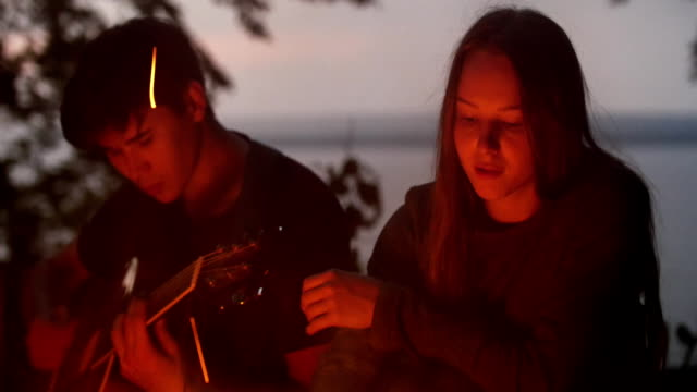 Young loving couple sitting by the bonfire and playing guitar in forest - video