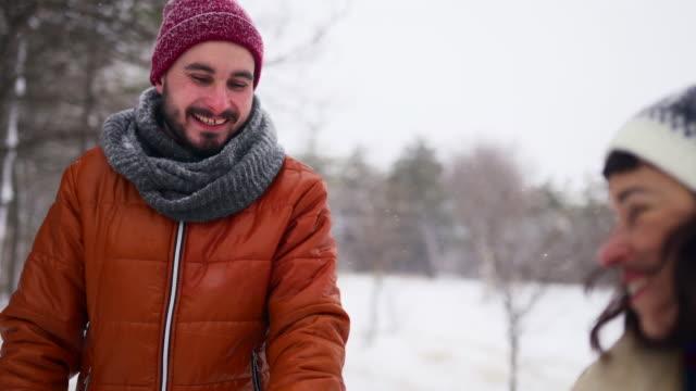 stockvideo's en b-roll-footage met jong liefdevolle paar wandelen in een park op sneeuwval. man na zijn vriendin handen vasthouden, genieten van sneeuw op de winterdag in besneeuwde bos. hipster vrouw in stijlvolle kleding leidt vriendje met de hand - lood