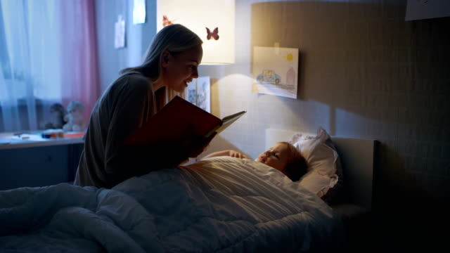 Young Loving Mother Reads Bedtime Stories to Her Little Beautiful Daughter who Goes to Sleep in Her Bed. video