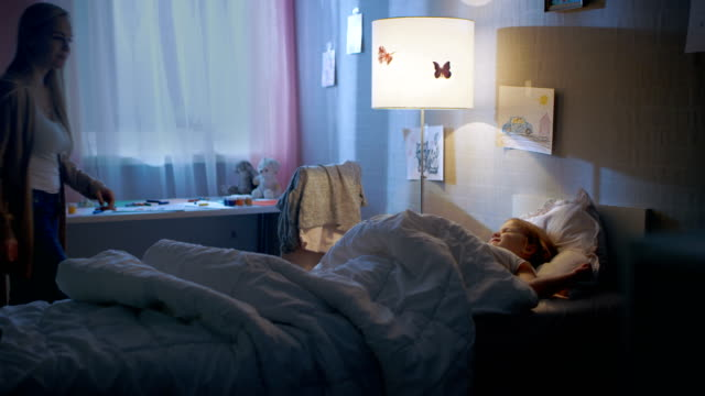 Young Loving Mother Tucks in Her Cute Little Daughter and Turns Off the Light. video