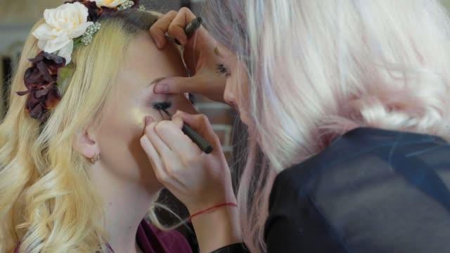 unga makeupartist sminkning på modellens ögon. - makeup artist bildbanksvideor och videomaterial från bakom kulisserna