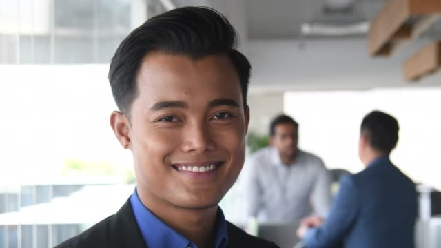 young malaysian businessman smiling towards camera - etnia malese video stock e b–roll