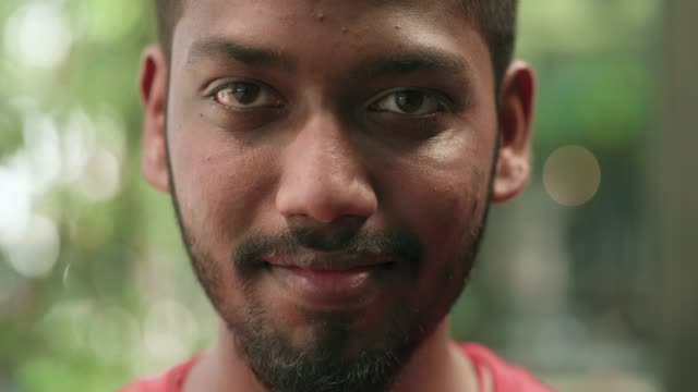 young malaysian man looking right at the camera - vicino video stock e b–roll