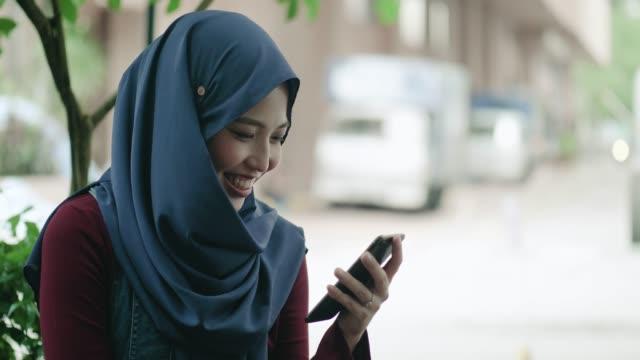 ung malaysisk kvinna med en mobiltelefon - hijab bildbanksvideor och videomaterial från bakom kulisserna