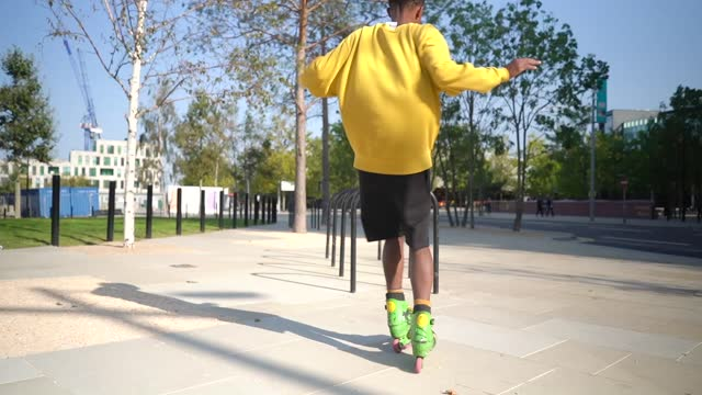 A young male adult practicing inline skating tricks