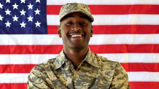 Young male African American soldier smiles confidently while standing in front of the American flag Handsome young African American male soldier crosses his arms and smiles cheerfully while standing in front of the American flag. veteran stock videos & royalty-free footage