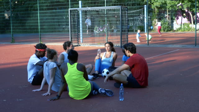 サッカーコートに座りながら話す若い男性と女性の友人 ビデオ