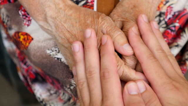 Young male arms comforting an elderly pair of old woman hands. Granddaughter and grandmother spending time together. Caring and loving concept. Close up Top view Slow motion video