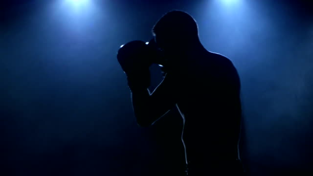 Young male athlete boxing in the studio visible in silhouette video
