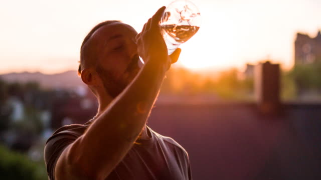 Young male athlete drinking water after finishing a run video