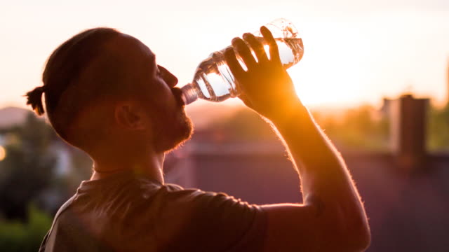 Young male athlete drinking water at sunset after working out video