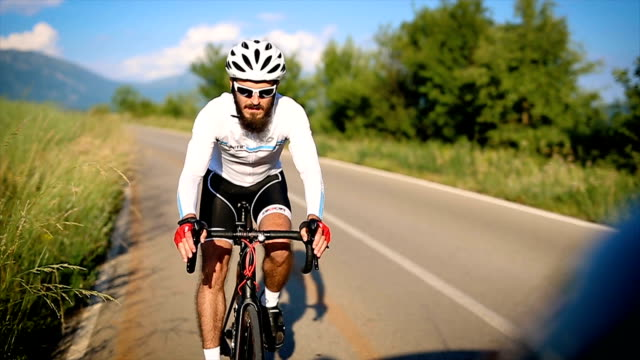 young male athlete road cycling on a country road - triatleta video stock e b–roll