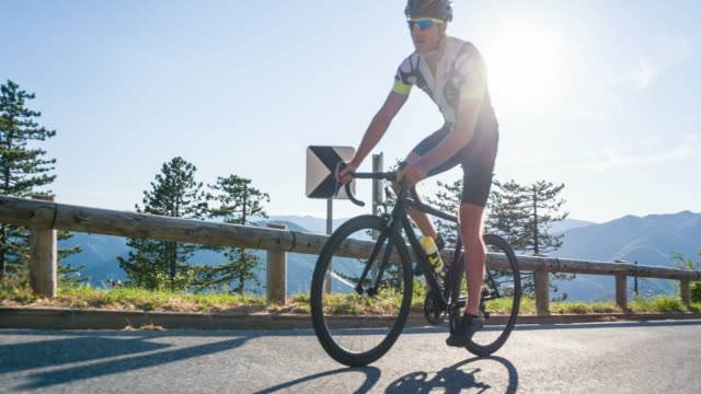 young male athlete road cycling on a mountain pass - triatleta video stock e b–roll