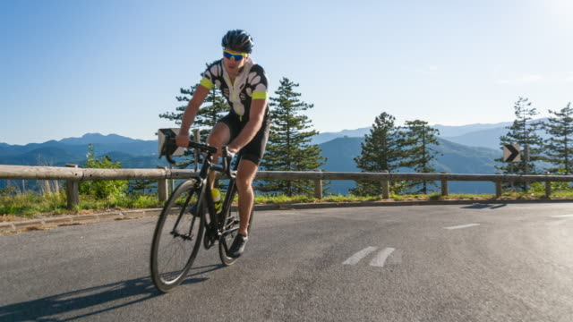 young male athlete road cycling on a mountain pass - passo montano video stock e b–roll