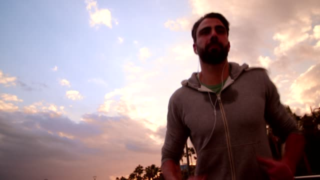 Joven atleta masculino correr y escuchar música al atardecer - vídeo