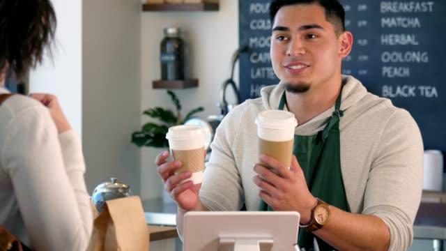vidéos et rushes de un barista jeune, mâle aide un client à décider sur la taille de sa boisson. - relation client