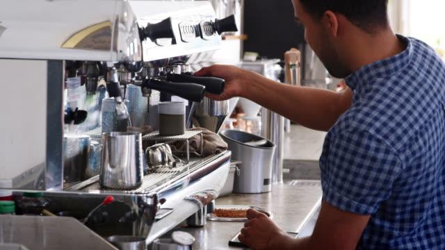 junge männliche barista zubereitung espresso in einem coffee shop - barista stock-videos und b-roll-filmmaterial