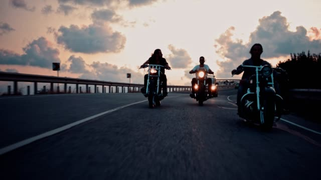 Young male bikers riding motorcycles on highway at sunset
