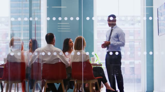Young male boss stands addressing business team at meeting Young male boss stands addressing business team at meeting face to face stock videos & royalty-free footage