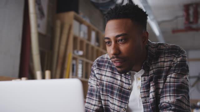 unga manliga företagare i verkstad för hållbara cyklar gör konton på laptop - småföretagande bildbanksvideor och videomaterial från bakom kulisserna