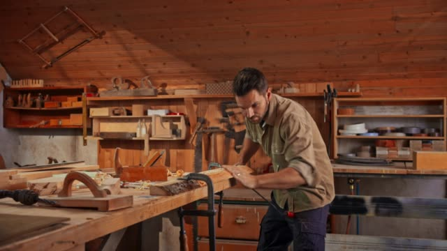 Young male carpenter using a drawknife to shape a piece of wood in his shop