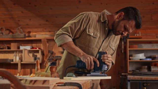young male carpenter using a jigsaw to cut a piece of wood in his shop - narzędzie do pracy filmów i materiałów b-roll