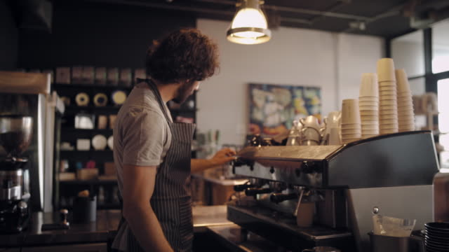 young male chef in apron making fresh coffee in takeaway cup and giving to customer - barista filmów i materiałów b-roll