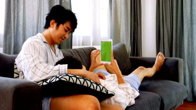 Young male couple looking at digital tablet