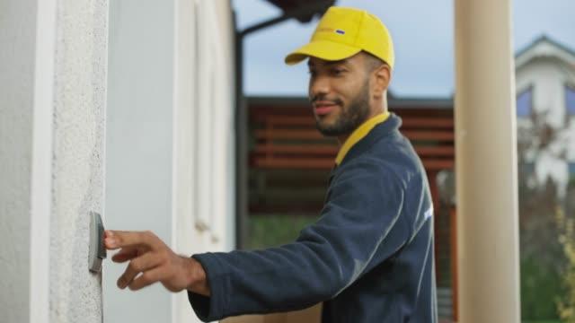 ung manlig kurir som levererar ett paket till en mans hem - ytterdörr bildbanksvideor och videomaterial från bakom kulisserna