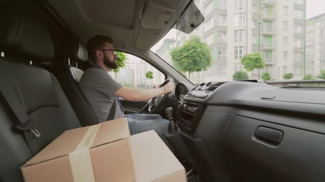 Young male courier driving delivery service car with parcels Young male courier with brown hair and beard wearing glasses, t-shirt and jeans driving delivery service car with lots of parcels on front seat. Concept of transportation and distribution post office stock videos & royalty-free footage