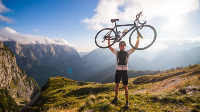 Young male cyclist victoriously raising bike on top of mountain video
