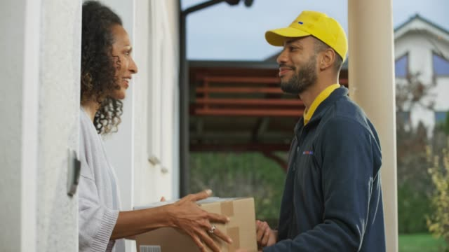 young male delivery service worker delivering the package to a woman - источник стоковые видео и кадры b-roll
