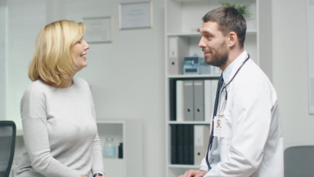 Young Male Doctor Consults His Mid Adult Female Patient. They are Talking Pleasantly. video