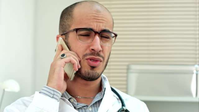 Young male doctor in glasses talking on mobile phone video